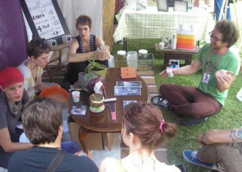 Plastic Aztecs socialize with guests offering them tea and selling zines/cds.